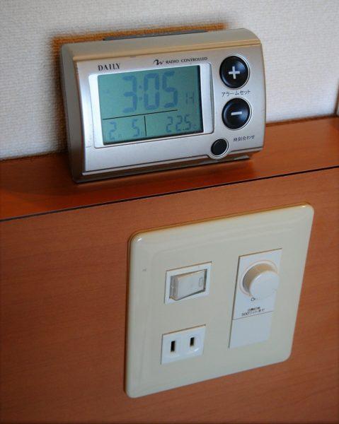 ベッドの頭付近にはコンセントもあるのでスマホ充電時に重宝。目覚まし時計もあります。