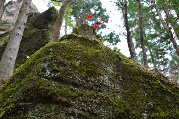 崖の上(赤矢印)にも石像がある。