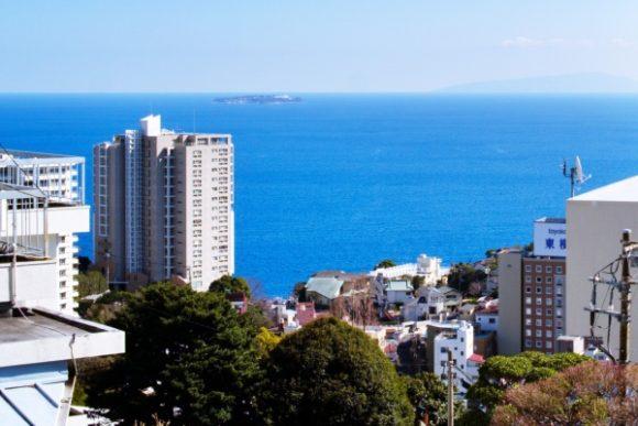 ホテルを目指す途中の街並み。初島と右手に伊豆大島がかすむ。