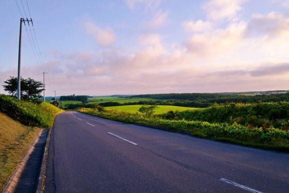 夕暮れの車道と酪農地帯。