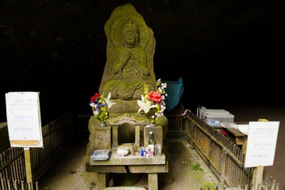 洞穴前には石像もある。